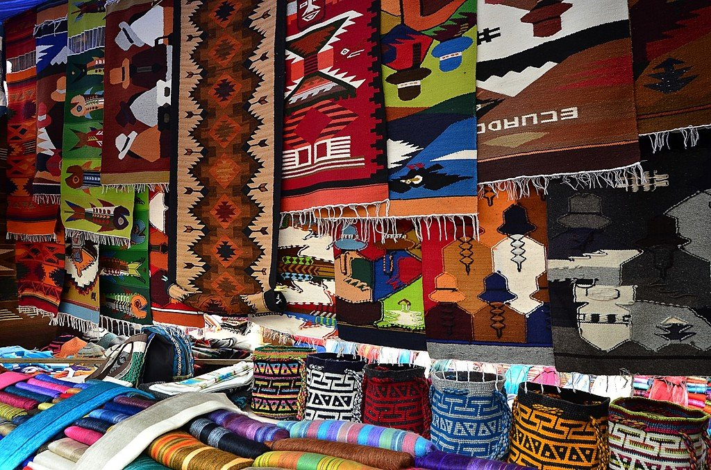 Colorful textile stall with hats in the popular Otavalo market.