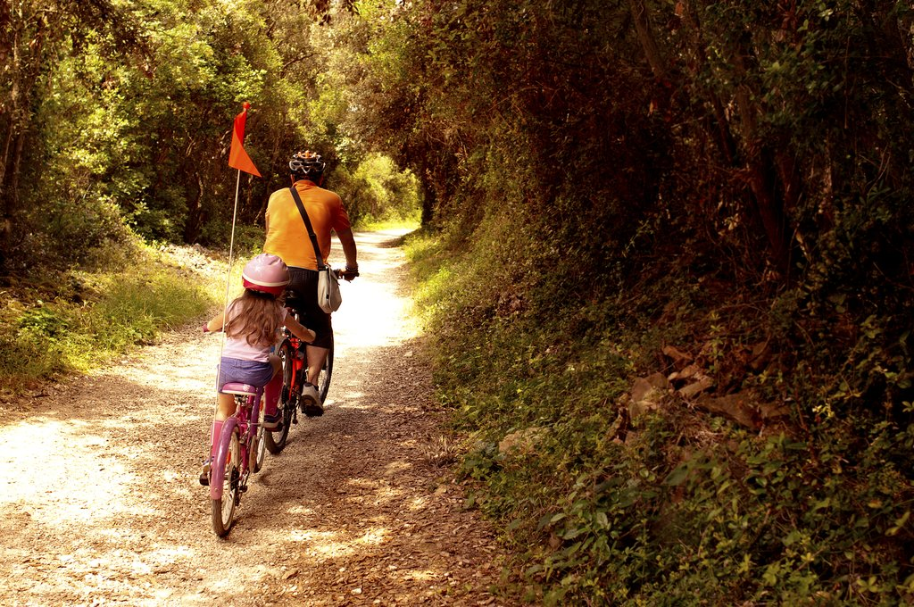 A father and daughter duo ride the forest-lined trails of Park šuma Zlatni Rt