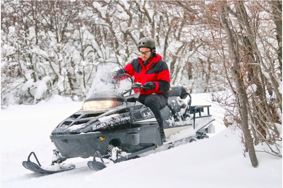 Snowmobile through winter forests and valleys