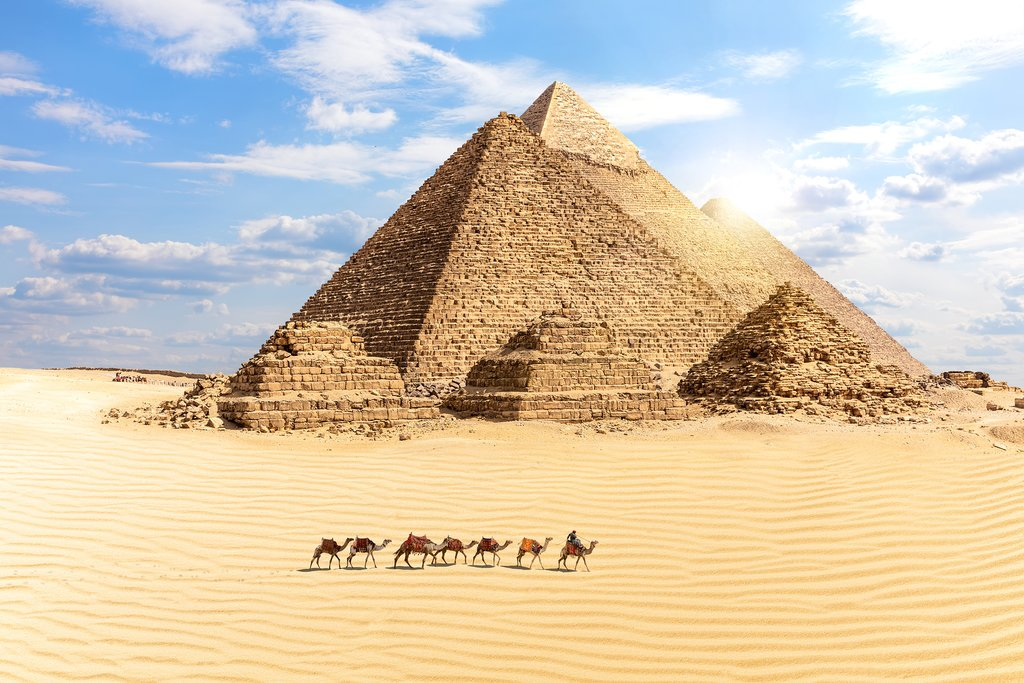 Egypt - Cairo - Great Pyramids of Giza and train of camels in foreground