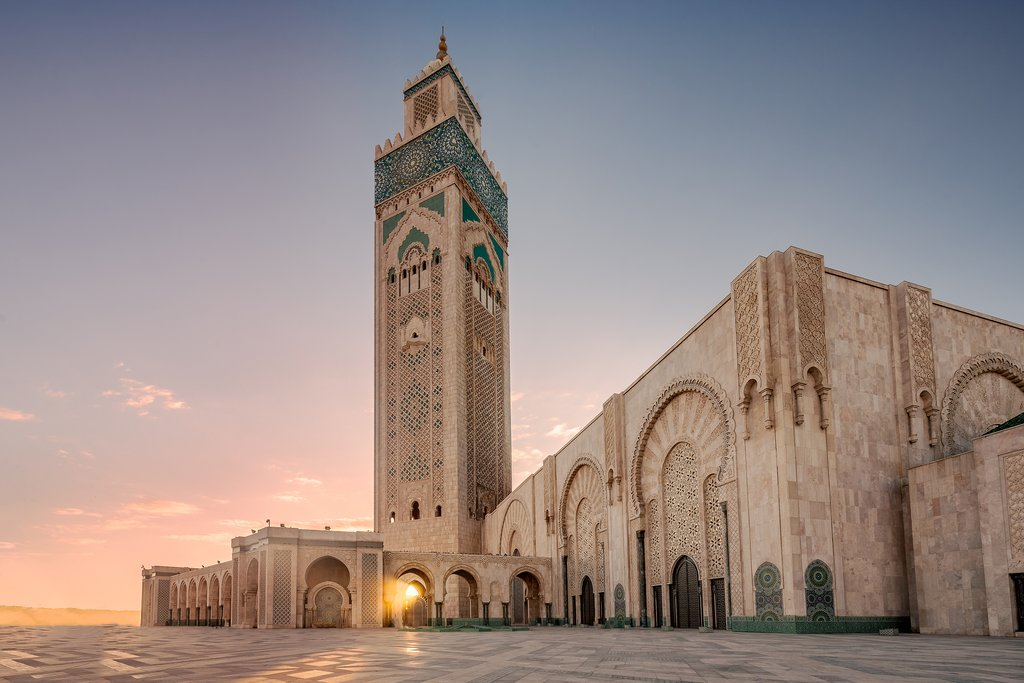 The rising sun peeks through the impressive Hassan II Mosque