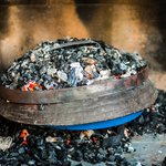 A peka dish cooking under hot coals