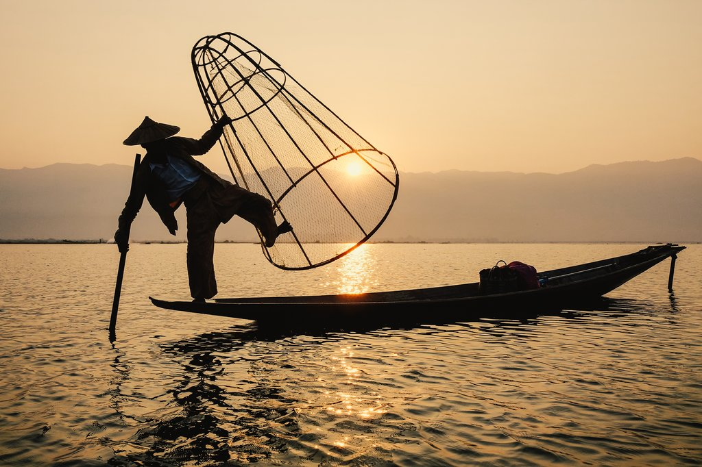 Intha man using the unique methods of rowing and catching fish on Inle Lake (Shan State).