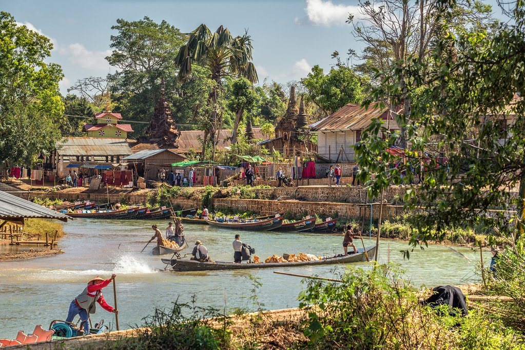 Tourists and locals travel by traditional long riverboats to the ancient city of Inwa