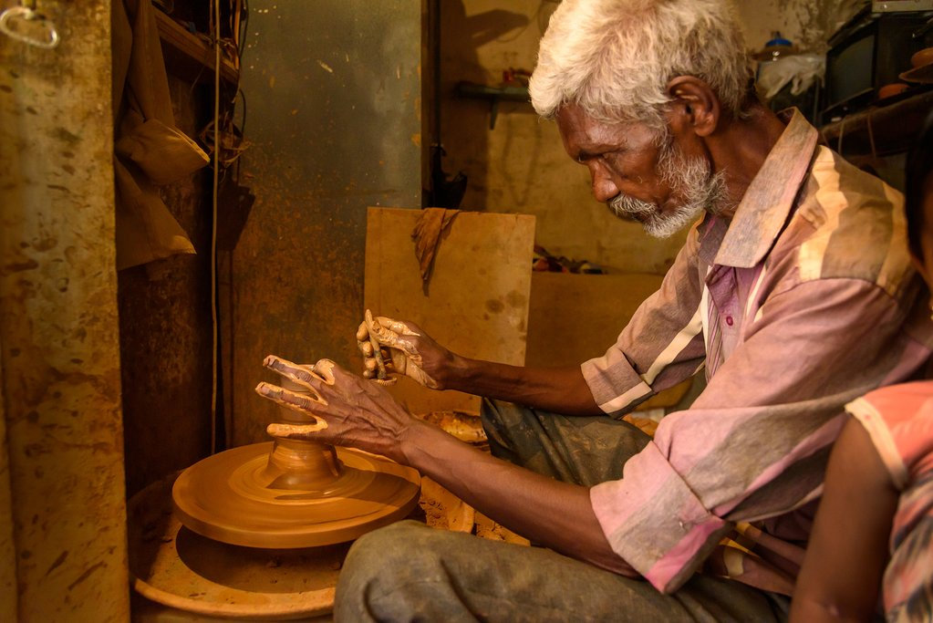 Indian potter making clay pots on pottery wheel in Pottery town is old place of Bangalore