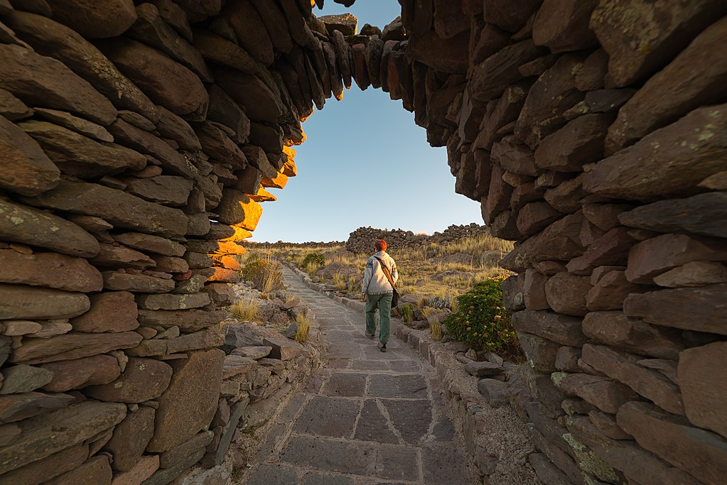 Traveler exploring Inca trails at sunset on Amantani Island