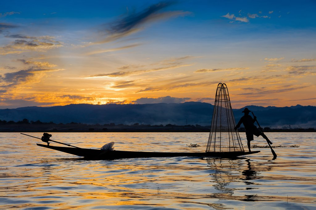 Fisherman demonstrating traditional fishing techniques at sunset