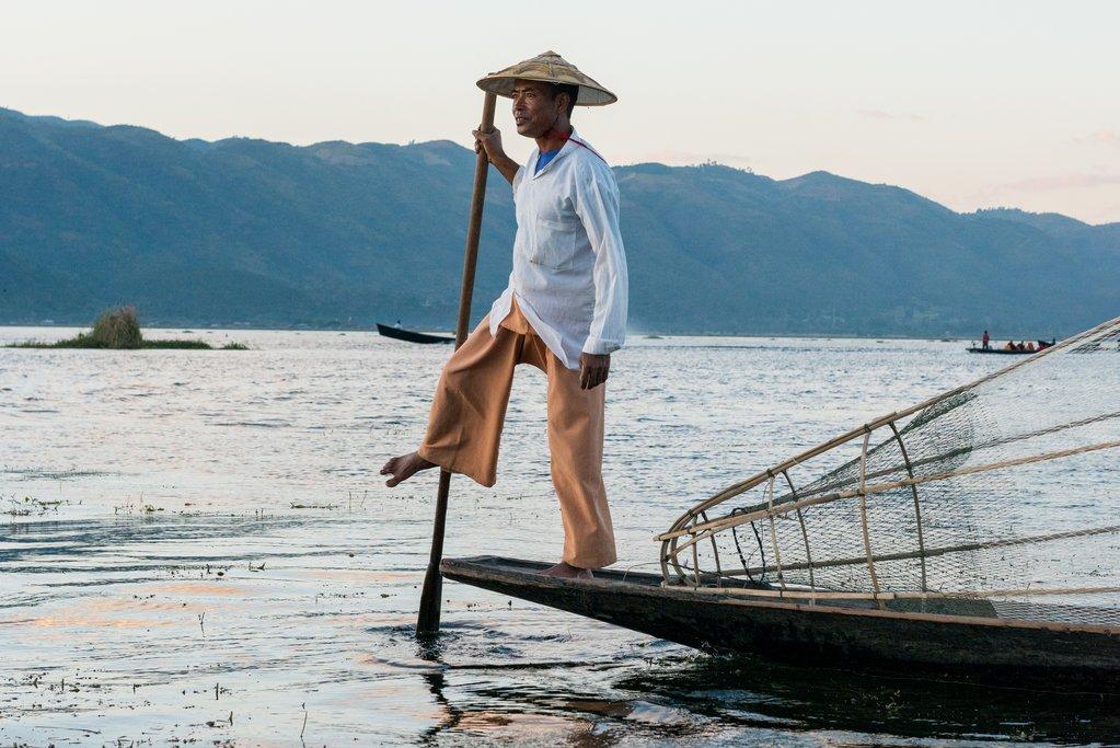 Horizontal picture of burmese fishermen posing with paddle during sunset at Inle Lake, Myanmar.