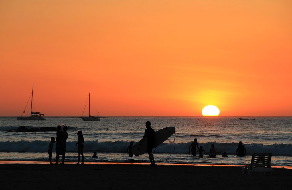 A surfer at sunset on Playa Tamarindo