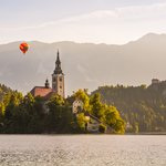 Hot air balloon flies over Lake Bled, Pilgrimage church, and Bled Castle in the background