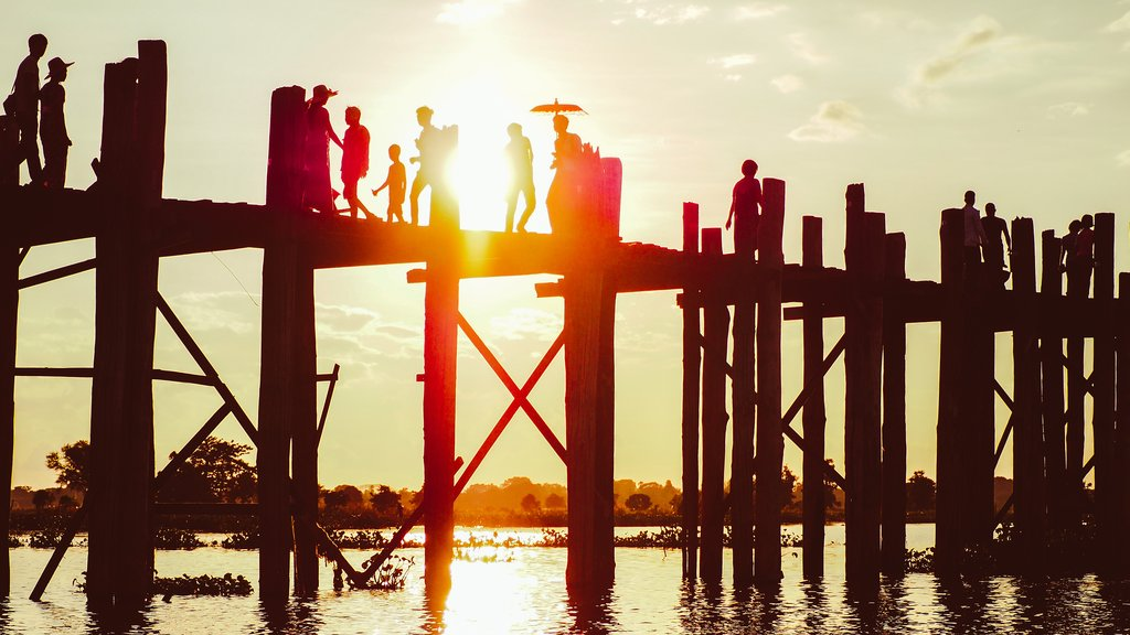 Silhouette of people walking on the U-Bein bridge in the evening in Amarapura