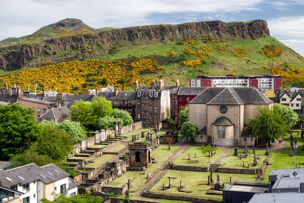 Salisbury crags over Edinburgh, Scotland. Church Canongate Kirk with graveyard