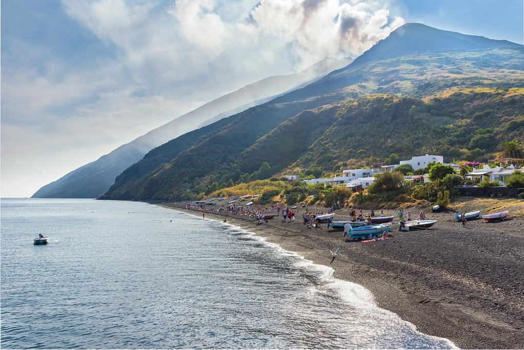 Italy - Sicily - Stromboli - People relax on the black sand beach with Stromboli in background