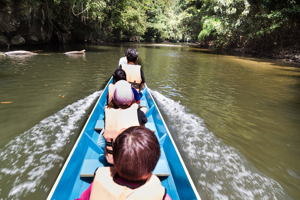 Riding long boat on Merlinau river to Wind and Clear Water caves