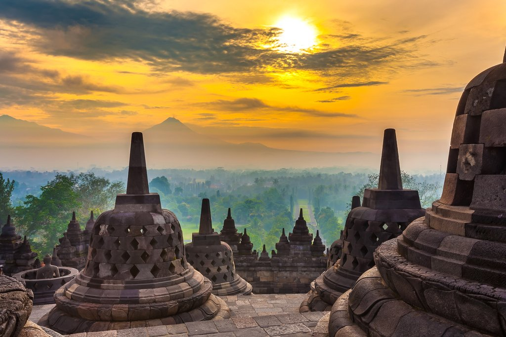 Taman Lumbini park from the height of the temple complex Candi Borobudur at sunrise in the fog. Candi Borobudur, Yogyakarta, Jawa, Indonesia