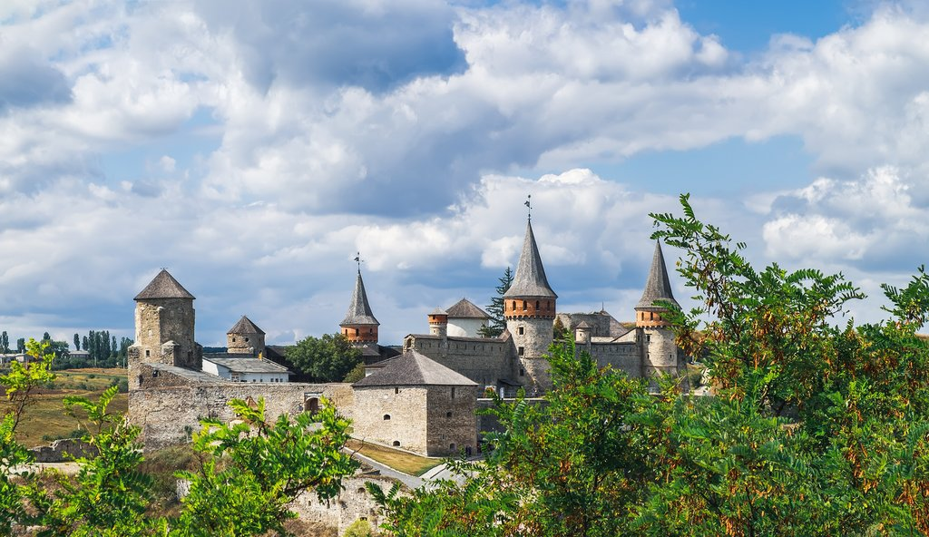 Old Kamianets-Podilskyi Castle under a cloudy blue sky, Ukraine