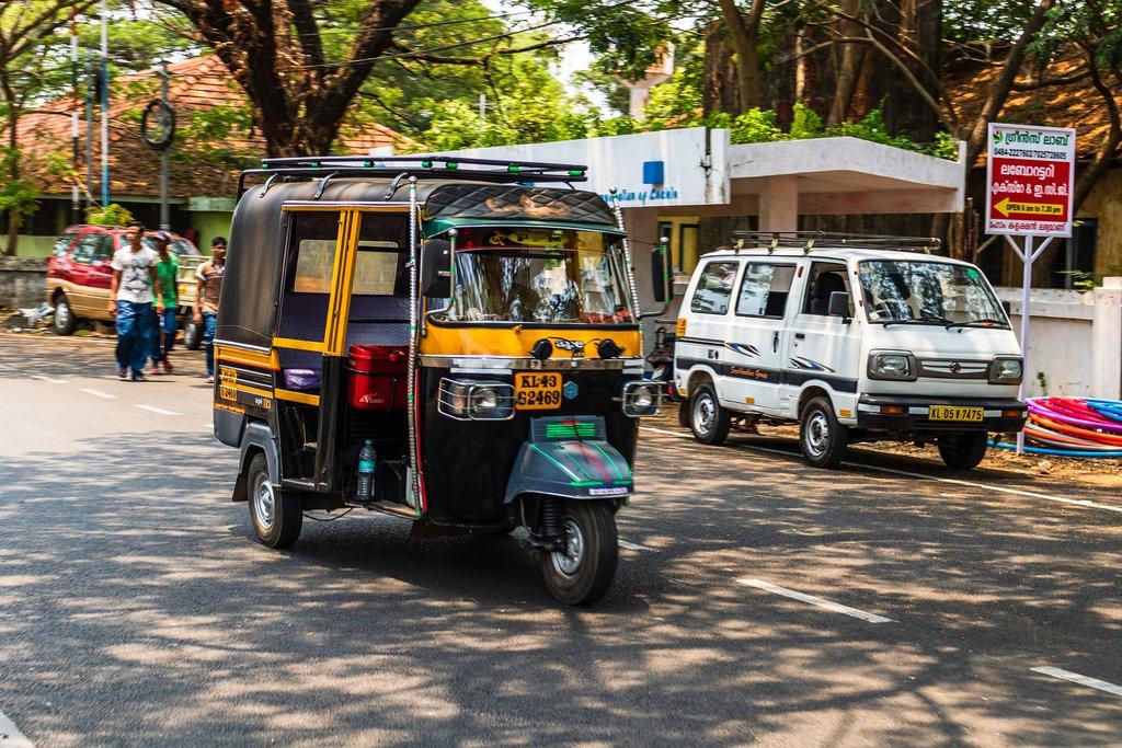 A tuk-tuk whizzing along a street in Cochin