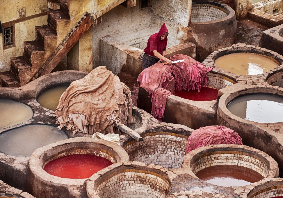 A worker trims a pile of leather hides in the Fes tannery