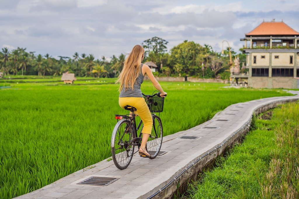 A woman cycling through a rice terrace in Ubud