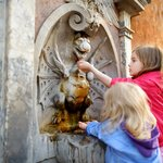 Two youngsters playing with a fountain
