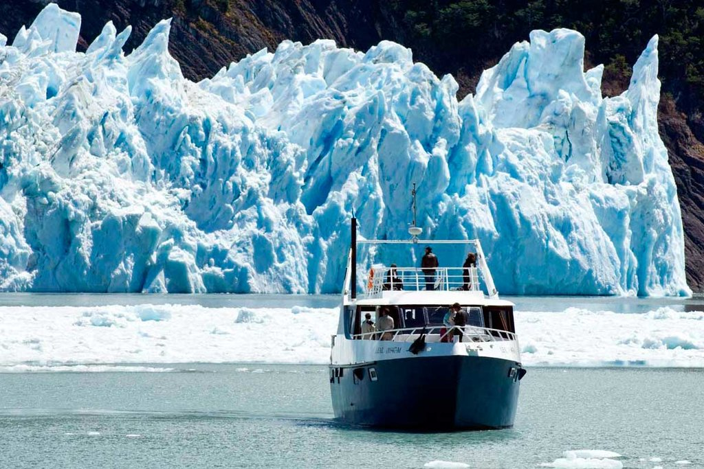 Sail under the towering ice walls of Perito Moreno Glacier.