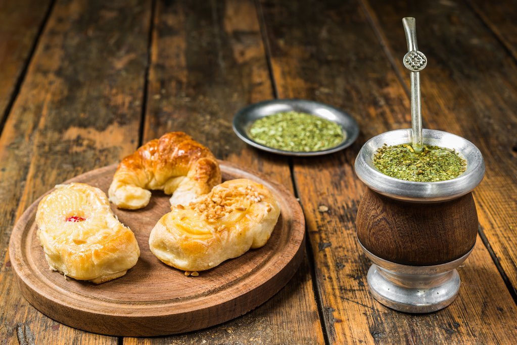 Traditional Argentinian yerba mate tea in calabash gourd and argentine pastries