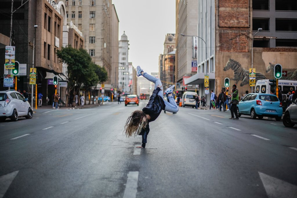 A woman does a handstand in a Johannesburg street