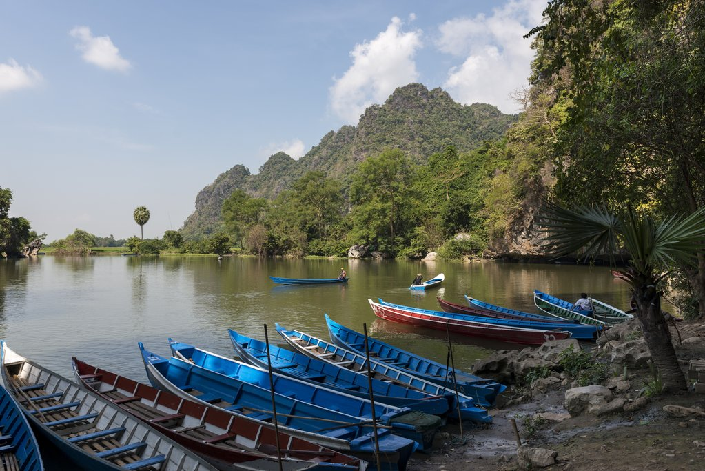 Save Download Preview HPA-AN, MYANMAR - 19 NOVEMBER, 2018: Horizontal picture of the exterior of Sadan Cave and some traditional boats in Hpa-An, Myanmar.
