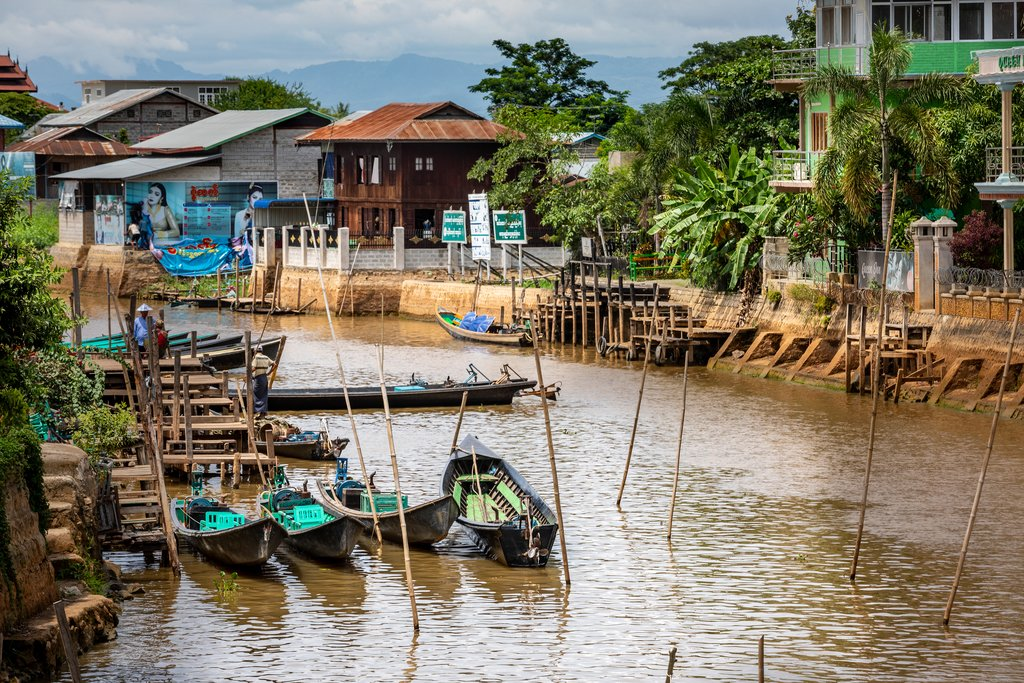 Canton de Nyaungshwe, Shan / Myanmar. July 31, 2019: Inle Boat Station in Inle Nyaung Shwe Canal. A series of fishing boats along the river generated by Inle Lake. Homes in the background.