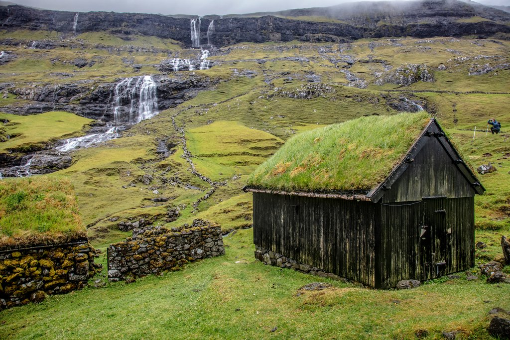 A sod roof house and waterfalls in Saksun