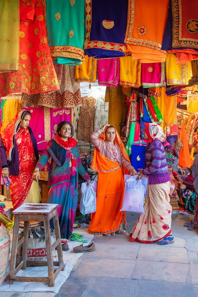 """Women in the Fashion District of Jaipur, known as """"The Pink City"""" because of its pink buildings. This fashion district of the city market sells colorful Sari material and decorations. 
