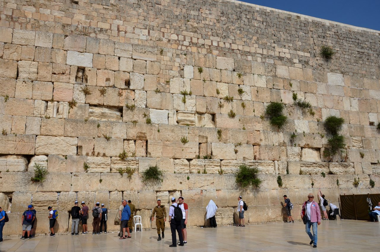 The Western Wall is an ancient limestone wall of the Old City of Jerusalem, and it is considered holy due to its connection to Temple Mount. The wall is part of the retaining wall erected by Herod in 20 BCE to support the vast plaza on which he rebuilt the Temple, so it is venerated as the sole remnant of the Temple on the Mount.  The wall is sometimes referred to as the Wailing Wall, likely due to the anguished prayers of ultra-Orthodox Jewish men as they read the Torah. | Photo taken by Rich W